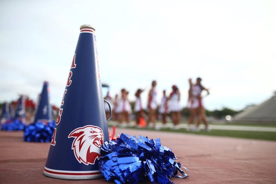 Gregory-Portland Wildcats cheerleaders prepare for 'Battle of the Bridge' high school football season starter against the Carroll Tigers.