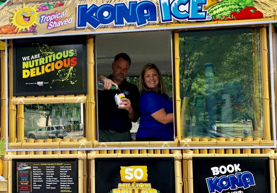 Ed and Sara Purdy aboard their Kona Ice truck. The couple sought out a business that could involve the whole family.
