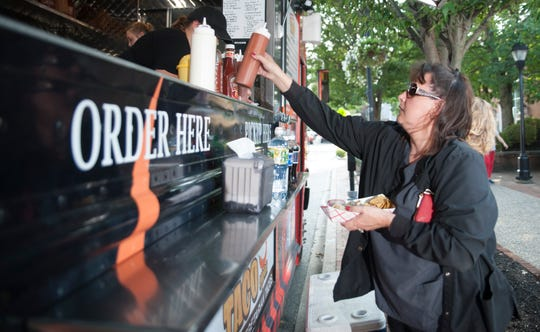 Dawn Bonsall of Lumberton purchases tacos from Jeremiah's Custom Cuisine food truck during the Moorestown Food Truck Festival on Wednesday, August 22, 2018.