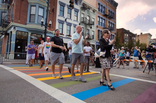 City and county leaders, along with representatives from the LGBTQ take part in celebrating for the new Pride crosswalk at Vine and 12th Street in Over-the-Rhine. City workers painted the rainbow colors. The project was paid for with private donations. At right is County Commissioner Denise Driehaus.