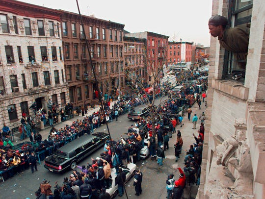 In this March 18, 1997 file photo, a man looks out his apartment window at the funeral procession for slain rapper Christopher Wallace, known as Notorious B.I.G., in the Brooklyn borough of New York. Considered one of the greatest rappers of all time, Biggie was shot to death on a Los Angeles street in a drive-by on March 9, 1997.