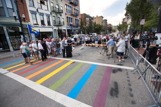 City Councilman Chris Seelbach, at podium, along with other city and county leaders, along with representatives from the LGBTQ take part in celebrating for the new Pride crosswalk at Vine and 12th Street in Over-the-Rhine.