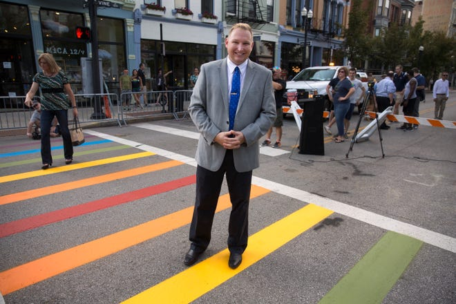 City Councilman Chris Seelbach, poses for a photo on the rainbow crosswalk at 12th and Vine Street in Over-the-Rhine, which he helped bring to the city.