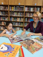 (From left), Isabella Reyes and GrandPal Stephanie Ives get ready to spend a half hour reading together at Johnson Park School in Princeton.
