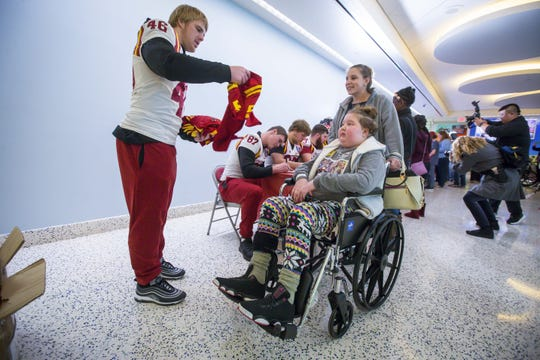 Iowa State player Spencer Benton hands a jersey to St. Jude Children's Research Hospital patient Alidiah of Tennessee Thursday, Dec. 28, 2017, in Memphis, Tennessee.