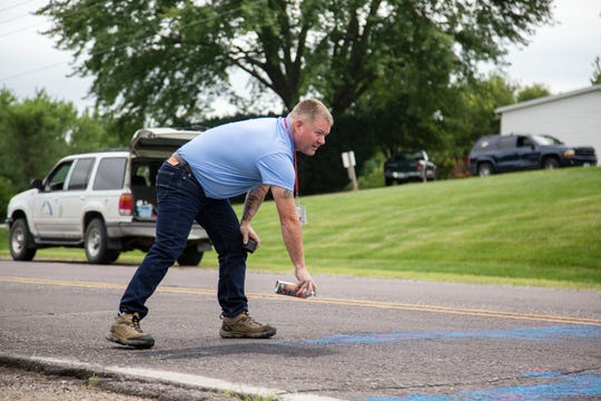 An employee for the city of Des Moines uses paint to cover graffiti painted on road earlier in the along Bloomfield Road on Thursday, Aug. 30, 2018, in Des Moines.