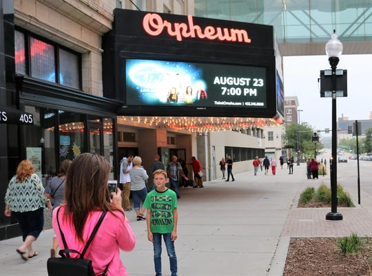 People take photos outside the Orpheum Theater.