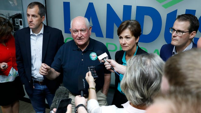 U.S. Agriculture Secretary Sonny Perdue, second from left, speaks to reporters Thursday as Iowa Gov. Kim Reynolds, second from right, looks on following a roundtable discussion at Landus Cooperative in Ames.