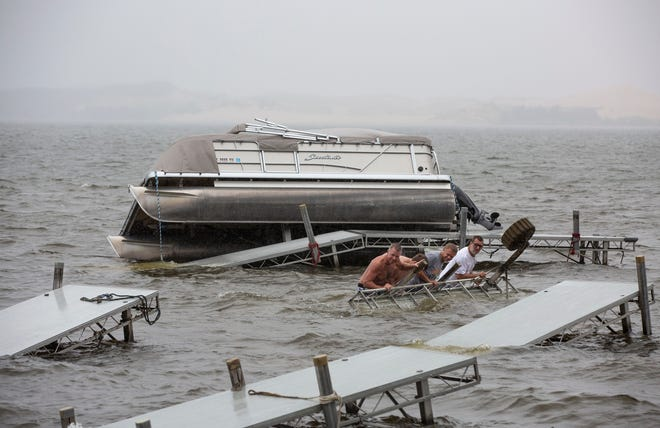 From left, Bill Heeren, Nick Bainbridge, Mark Heeren, and Brian Batey work to free a pontoon boat from a damaged dock on Wednesday, Aug. 29, 2018, in Silver Lake, as a wave of thunderstorms with strong winds caused widespread power outages and scattered damage across western and northern Michigan.