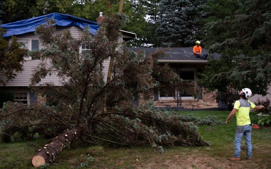 Clean up from a severe thunderstorm in Kent County, Mich., takes place on Wednesday, Aug. 29, 2018. The storm caused a tree on Springbrook Drive to collapse into a house.