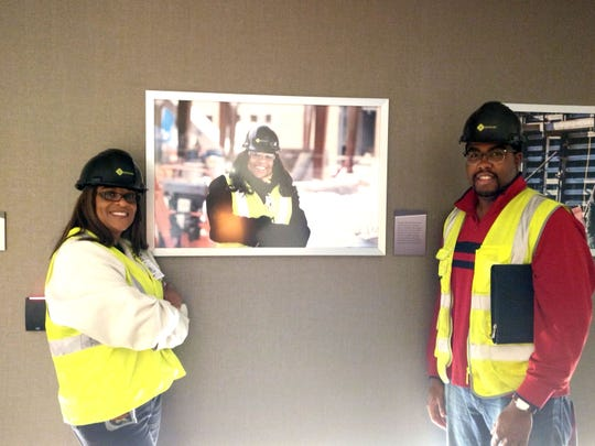 Adrienne Bennett with her son A.K., both of of Benkari Plumbing of Detroit, pose with a photo of her at Little Caesars Arene where they worked on a plumbing contract.
