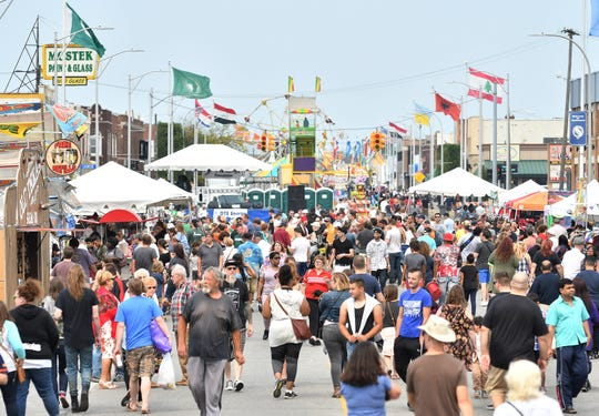 People walk on Joseph Campau Avenue during the Hamtramck Labor Day Festival in Hamtramck, Mich. on Sept. 4, 2017.