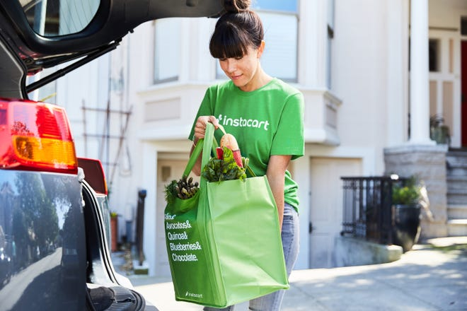 A woman puts groceries in her car for Instacart. Sam's Club said Thursday that it had partnered with Instacart to bring home delivery to the Metro Detroit area.