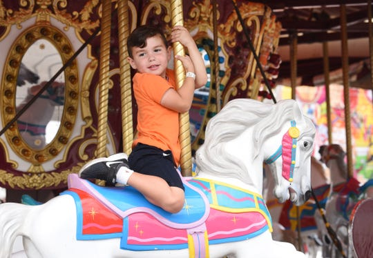 Donovan Hindo of West Bloomfield Township rides the carousel at the Michigan State Fair.