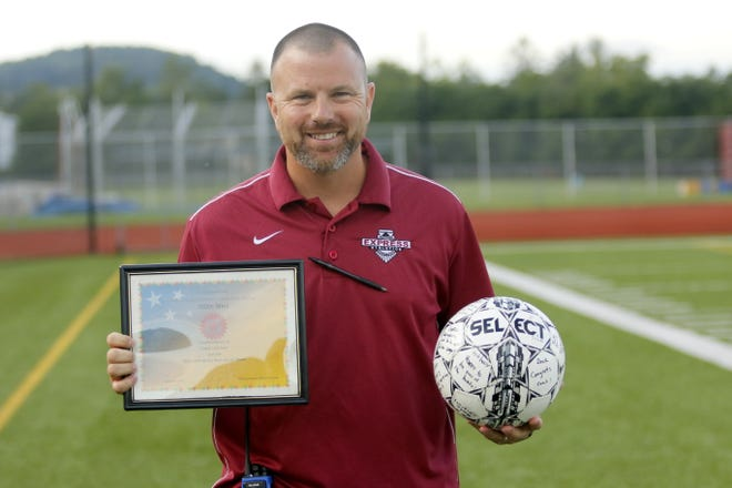 Elmira boys soccer coach Derek Hamilton poses with a plaque and ball he received after reaching 100 career wins Aug. 30 with the Express' 2-0 victory over Corning at Ernie Davis Academy.