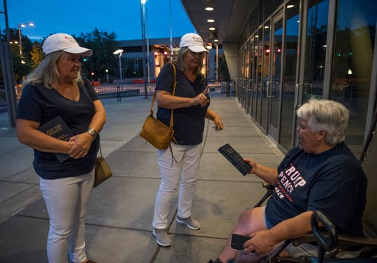 "Trisha Hope, middle, hands Sharon Anderson a book she recently published titled ""Just The Tweets"" which chronologically list all the tweets from President Trump. Anderson was the first inline to see President Trump at the Ford Center in Evansville, Ind. on Wednesday August 29th, 2018."