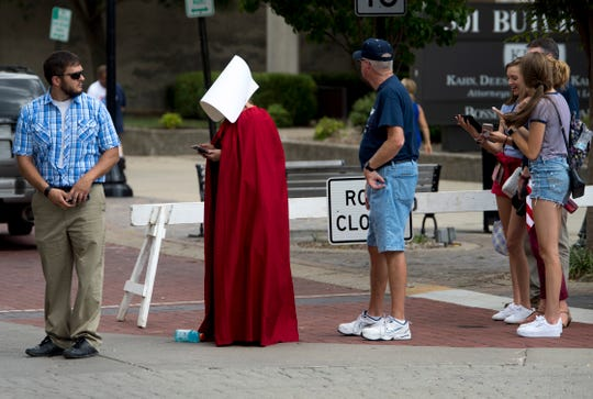"""A woman garbed in a """"Handmaid's Tale"""" cloak and headpiece stands in line to attend President Donald Trump's campaign rally in Evansville last week. The TV show costume, designed by Henderson native Ane Crabtree, has become a symbol of protest across the country."""