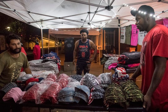 """Caristian Fletcher, middle, directs Kristian Walden, left, and Joe Gilmore, right, on the setup of their """"Trump Gear 2020"""" vendor booth outside the Ford Center on 6th and Main Street the night before President Donald J. Trump plans address a crowd of 11,000 people in downtown Evansville."""