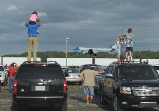 People watch from their cars as President Donald Trump arrives on Air Force One at Tri-State Aero in Evansville, Ind., Thursday afternoon, August 30, 2018.