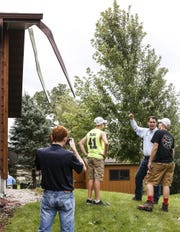 Wisconsin Governor Scott Walker (second from right) talks to Cade and Carson Kemmel Thursday about their North Street house, which damaged in Brownsville.