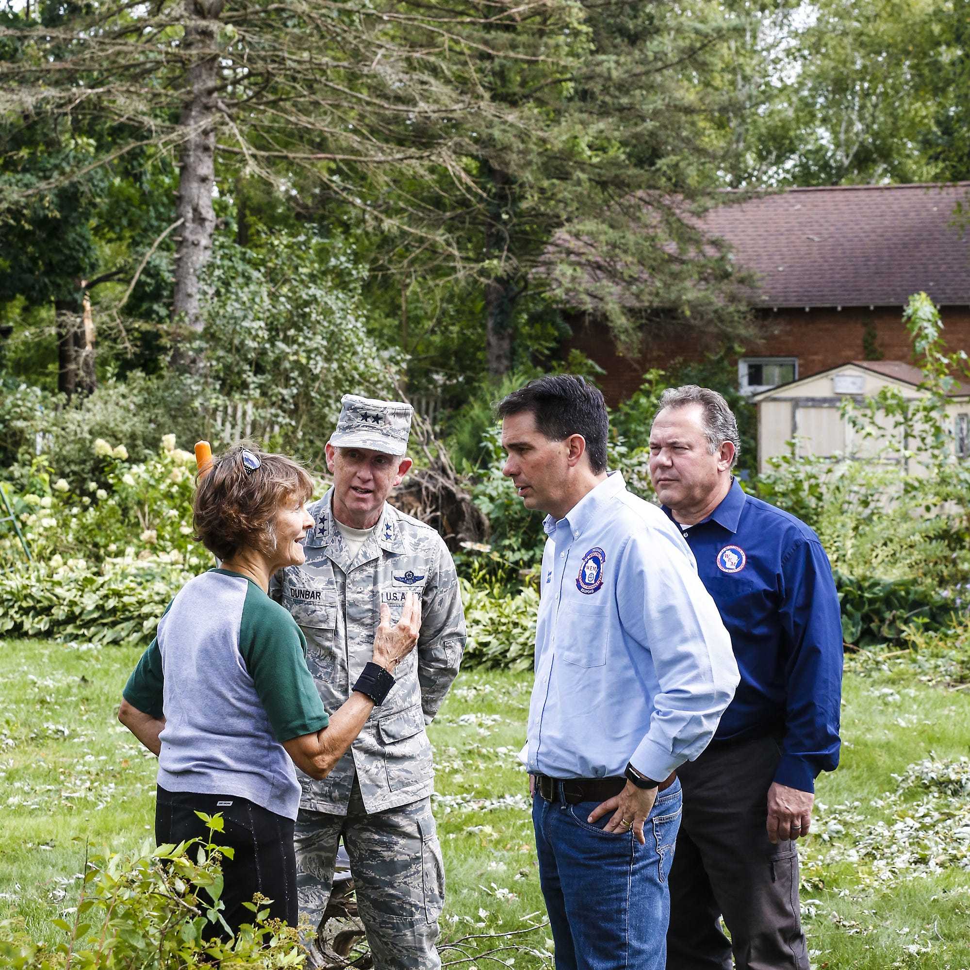Jo Ann Gouin talks about damage her house sustained during the tornadoes with, from left, Donald Dunbar of the Wisconsin National Guard, Wisconsin Governor Scott Walker and Brian Satura of Wisconsin Emergency Management Thursday in the backyard of her Highland Street house in Brownsville.