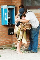 A family comforts each other and makes a phone call letting people know they are safe after an F5 tornado ripped through the small community of Oakfield on June 12, 1996.