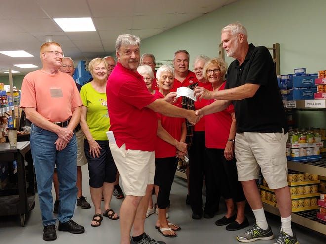Elks Exalted Ruler Mike Mowry presents a check to Food Pantry Director Roy Wilhelm. Others pictured include, from left, Jim Faist, Nancy Francis, Mark Foos, Diann Hamons, Richard and Ann Foos, Rick Franks, Mary Beaston, and Jeff and Pastor Jody Rice.