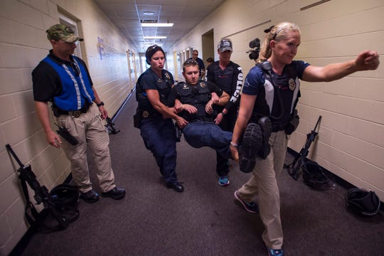 Fort Collins police detective Tessa Jakobsson leads as she and other officers carry Officer Brandon Barnes while participating in active shooter training on Wednesday, July 25, 2018, at Fort Collins High School in Fort Collins, Colo.