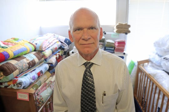 Dave Pietenpol, director of the Ecumenical Partnership for Housing,  stands in one of the partnership's storage rooms full of supplies for the partnership's transitional housing clients.