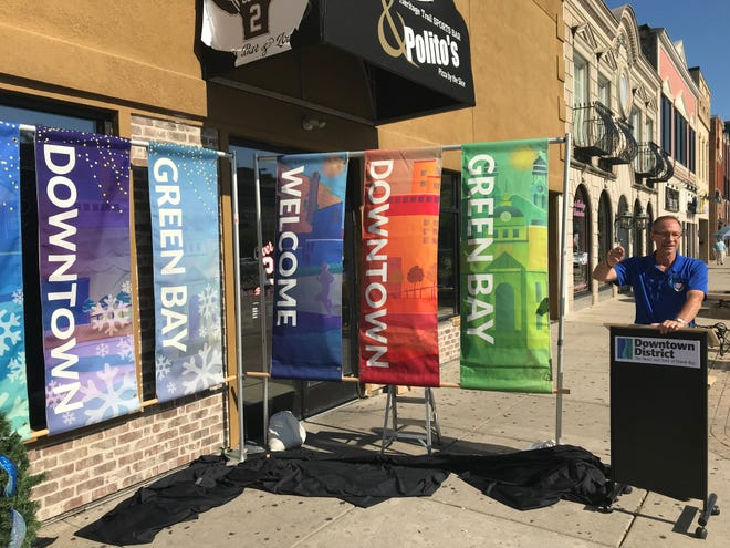 Downtown Green Bay Inc. Executive Director Jeff Mirkes shows off new light pole banners bought and installed in 2018 to further beautify and improve downtown Green Bay.