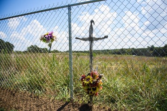 A cross and flowers are fixed on a fence on Todd Kohlhepp's property in Woodruff the day online auction winners pick up their property on Thursday, Aug. 30, 2018.