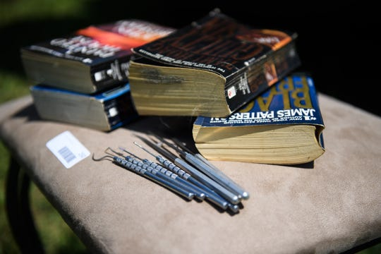 Brandi Wroten shows the books, stool and dental tools she won at the online auction for the property of serial killer Todd Kohlhepp in Woodruff on Thursday, Aug. 30, 2018.