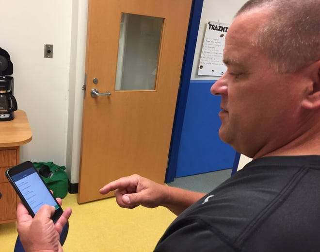 Eastside High School athletic trainer David Webb demonstrates the HitCheck app, which helps trainers as an assessment tool in their treatment of concussions.