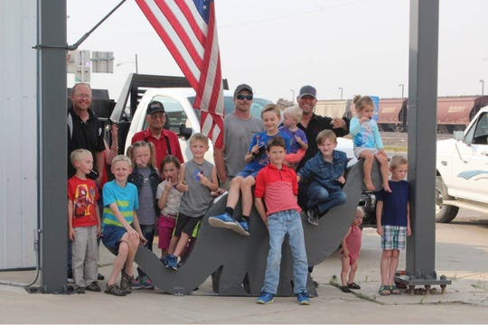 Family and friends celebrate the installation of a baby Brontosaurus at Simons Petroleum gas station in Shelby. They worked on the dinosaur for about two years.