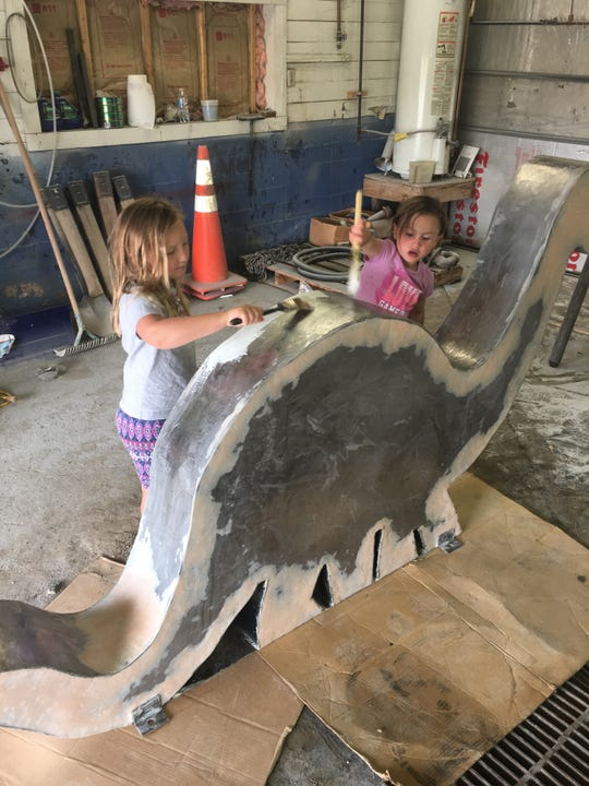Bella and Linden Aikins paint a Brontosaurus for the Simons Petroleum gas station in Shelby.