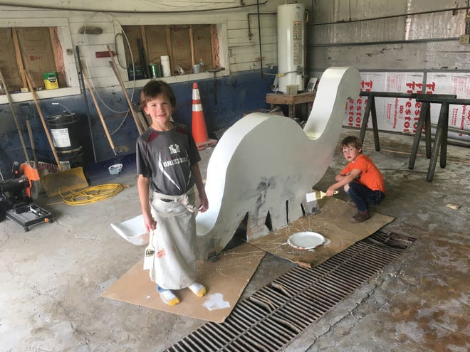 Kolben and August Aikins paint a Brontosaurus for the Simons Petroleum gas station in Shelby.