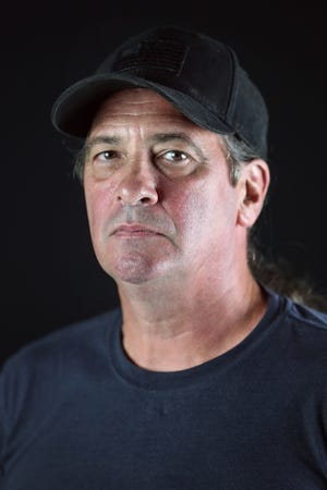 Steven DeLong poses for a picture in the IndyStar studio in Indianapolis, Wednesday, Aug. 29, 2018. DeLong's parents were victims of a bombing at Speedway High School, one of eight that occurred over a span of six days in September 1978. Both Carl and Sandra DeLong survived the bombing but Carl lost a leg and faced a long road to physical and mental recovery. Carl committed suicide in 1983, after struggling with post-traumatic stress disorder stemming from the bombing and his service in Vietnam. Steven said his father had not experienced war-related PTSD prior to the bombing.