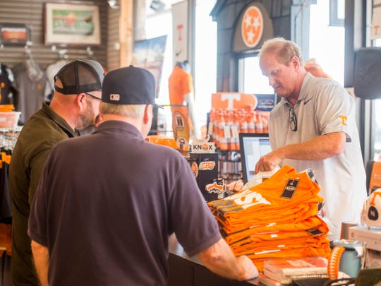 HoundDogs of Knoxville owner Don Lowe, right, checks out items for customers on Wednesday, August 29, 2018.