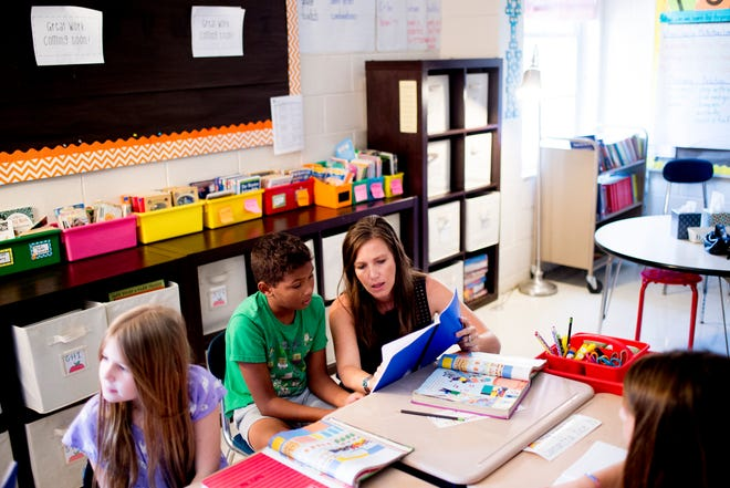 """Third-grade teacher Nikki Sawyers helps Thomas L. with his """"quick write"""" reading comprehension exercise at Blue Grass Elementary School in West Knoxville, Tennessee on Wednesday, August 29, 2018. Forty percent of third graders in Knox County Schools are reading at grade level as literacy continues to be a top priority for the school district and Superintendent Bob Thomas."""