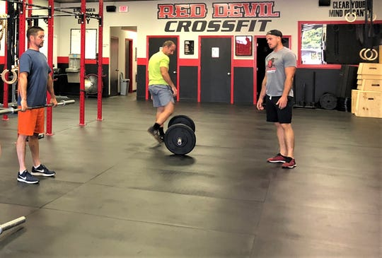 Tristan Smith coaches a Workout of the Day (WOD) on Aug. 30 with Lance Pratt, left, and Aaron Cadle at Red Devil CrossFit.