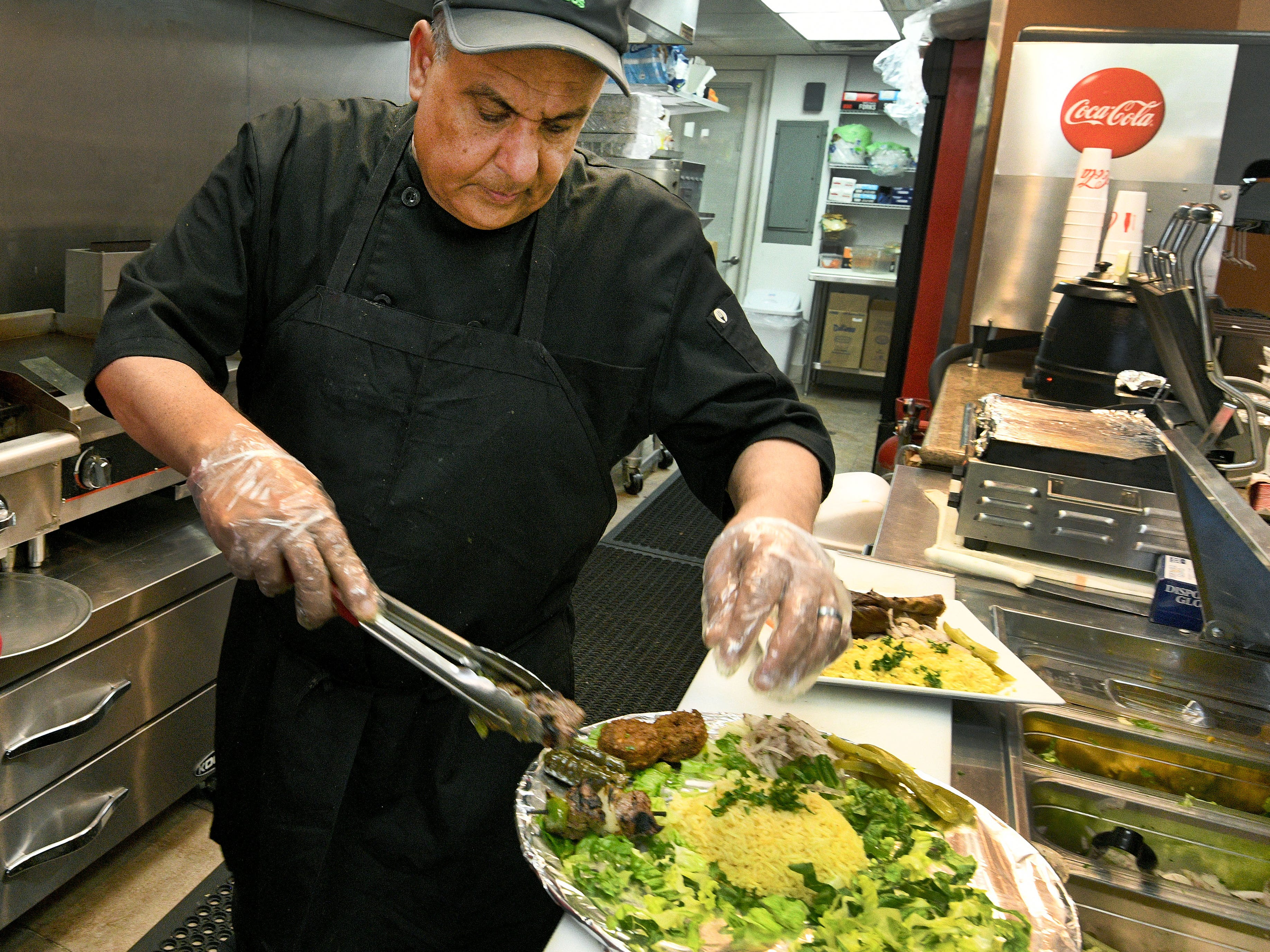 Ashraf Yousef assembles a mixed grill platter at Sahara Mediterranean and Indian restaurant on James Agee St. Tuesday, August 28, 2018.
