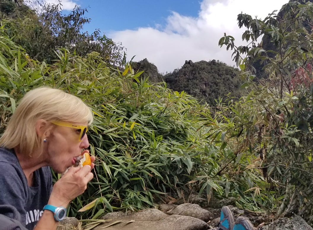Kirby Adams eats a passionfruit after climbing Huayna Picchu