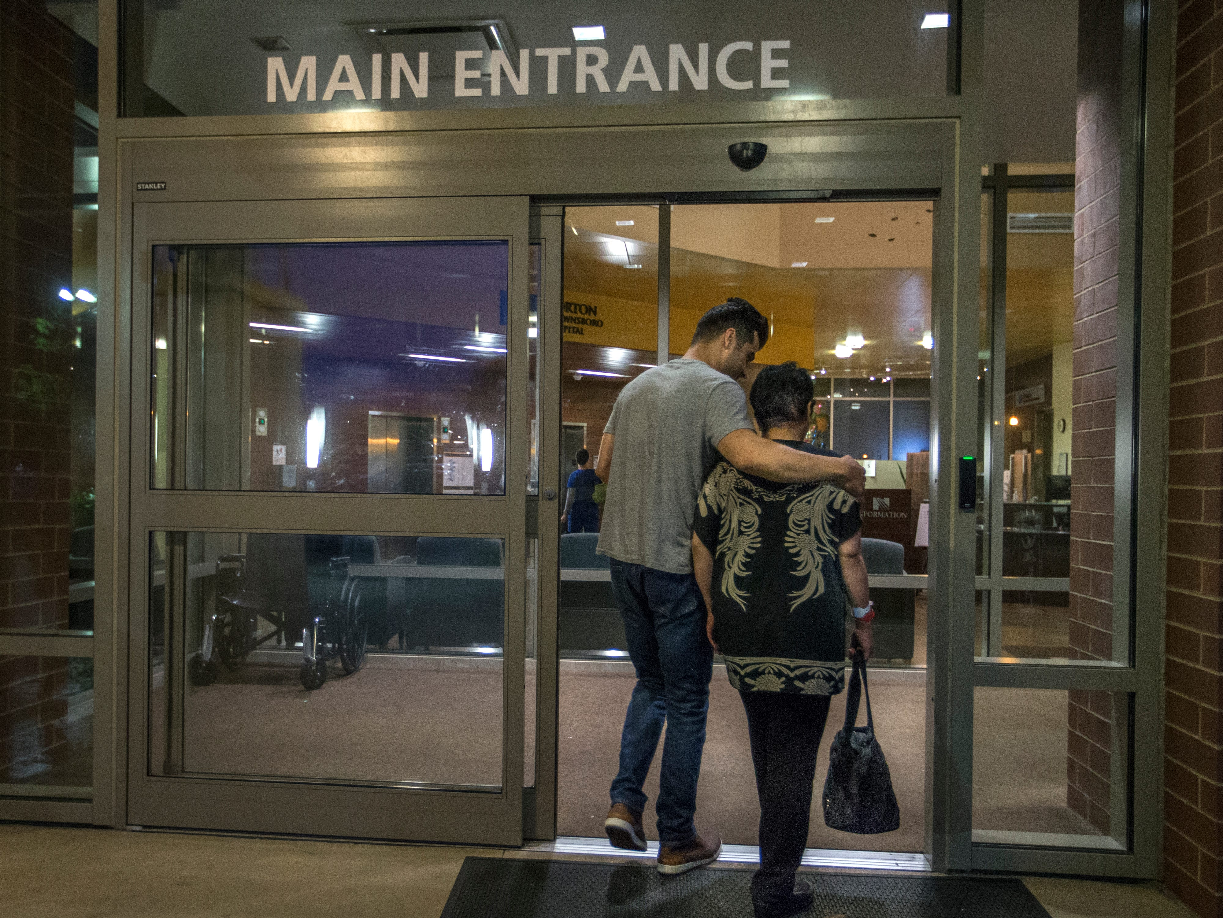 Mehran Jafari helps his mother Marzieh Taheri into Norton Brownsboro Hospital before sunrise. Taheri, an Iranian national, is in Louisville being treated for deadly radiation necrosis. Aug. 30, 2018.