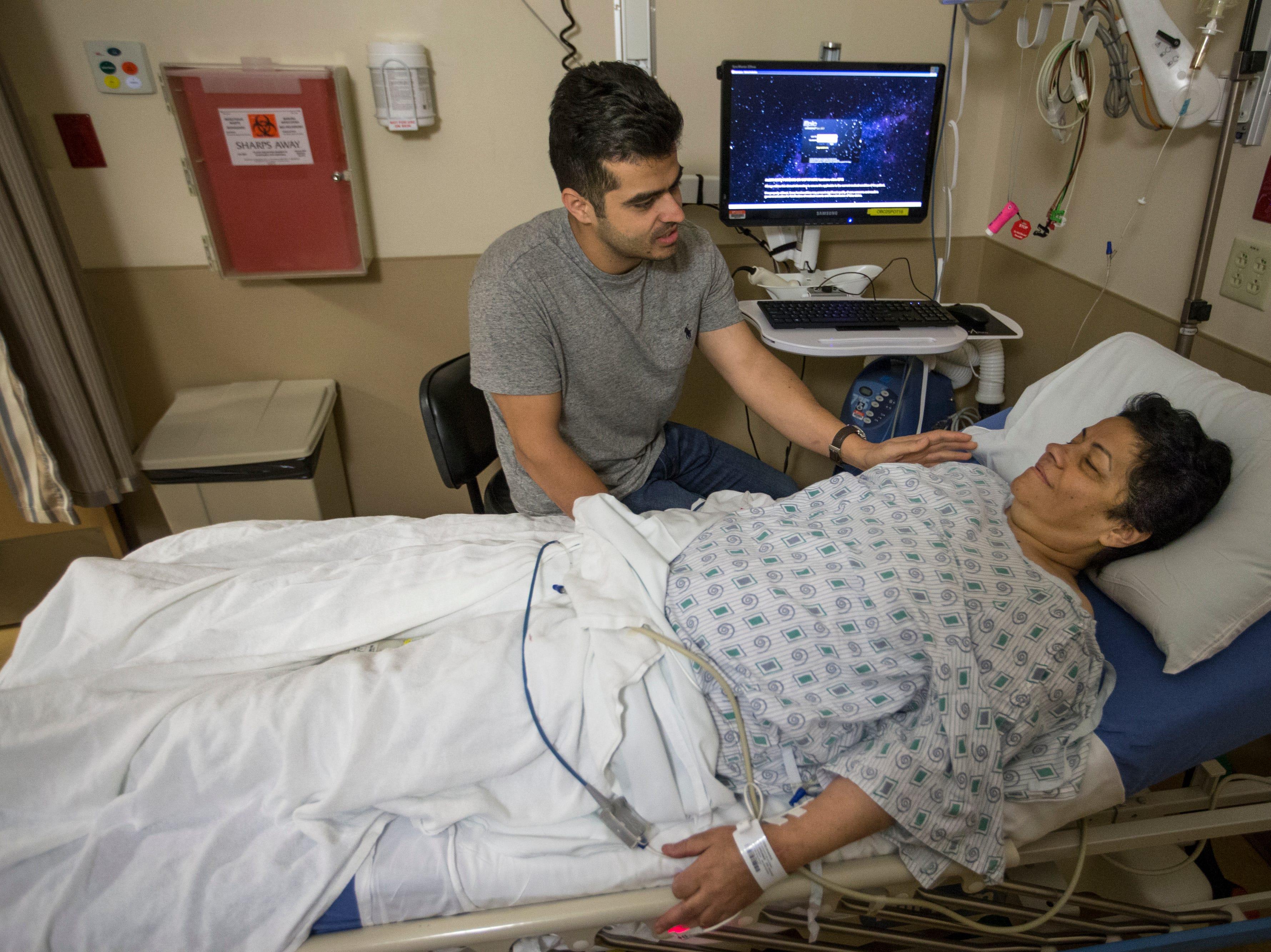 Mehran Jafari comforts his mother, Marzieh Taheri, as she awaits treatment for radiation necrosis at Norton Brownsboro Hospital. Aug. 30, 2018.