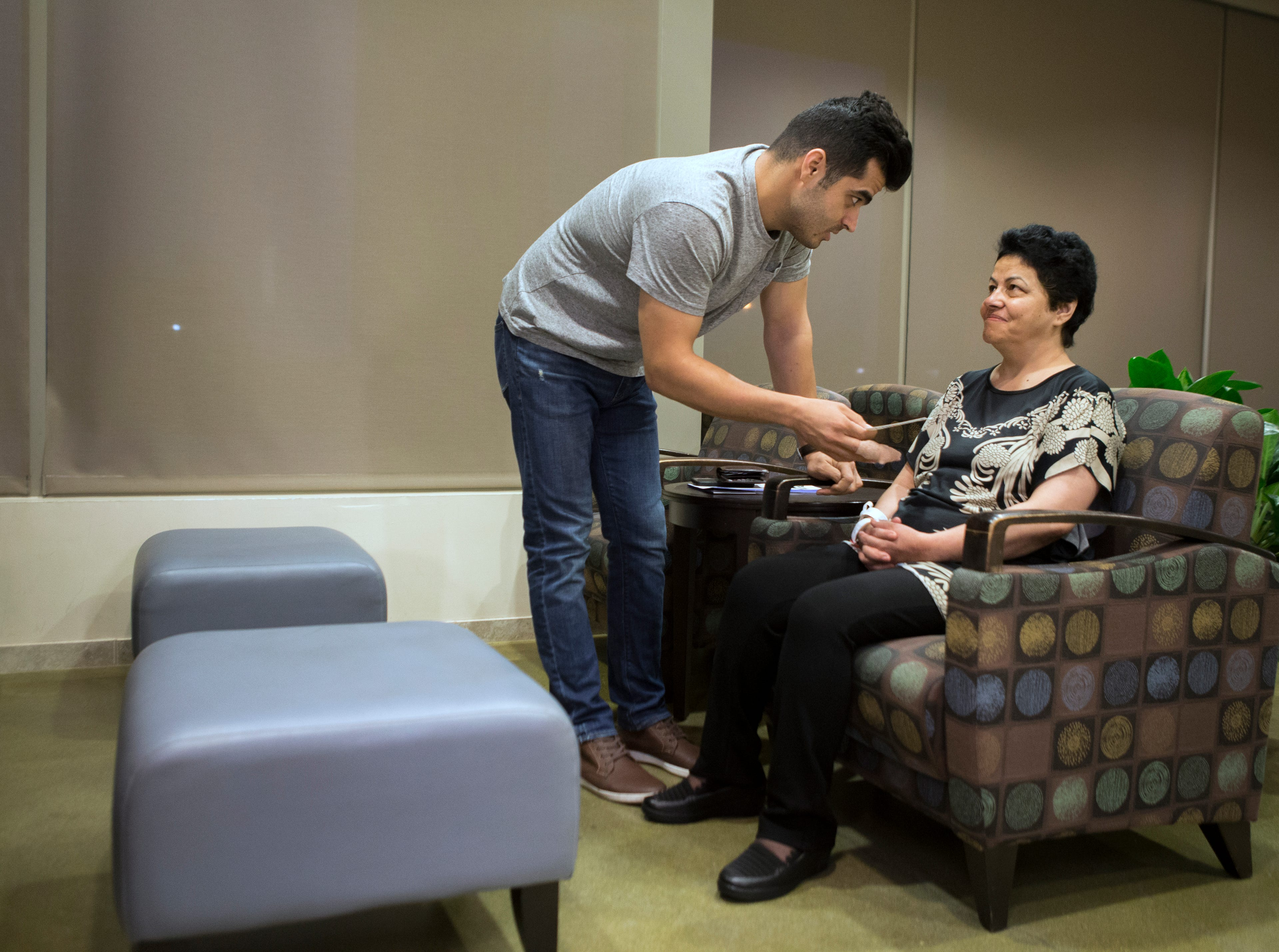 Mehran Jafari, left, talks with his mother Marzieh Taheri in the waiting room of Norton Brownsboro Hospital. Taheri received special permission to travel from Iran to receive treatment for radiation necrosis. Aug. 30, 2018.