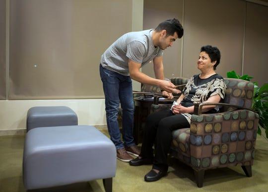 Mehran Jafari, left, talks with his mother Marzieh Taheri in the waiting room of Norton Brownsboro Hospital.