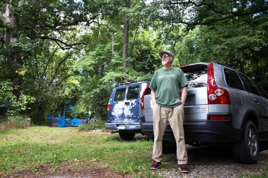 "Robert Park stands in his driveway Thursday, Aug. 30, 2018, in front of the entrance to ""The Blue Loop,"" a 1,000-foot art installation he built in the woods he owns behind his home, where he's lived for nearly 40 years.  In May, the township ordered him to clean up the place, including removal of the installation he's worked on for over two years.  A hearing is set for Oct. 31 in Clinton County District Court to determine if it's art, or junk.  Park has a bachelor's in fine arts from Michigan State University, where he earned a teaching certificate, and had a solo show in the fall of 2017."