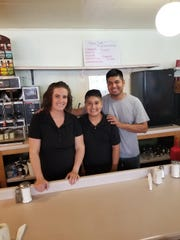 Pedro and Branda Vieyra pose behind the counter with their son Jesus at Marshfield Family Restaurant on Wednesday. The Vieyras re-opened the restaurant after it had been closed about a month.