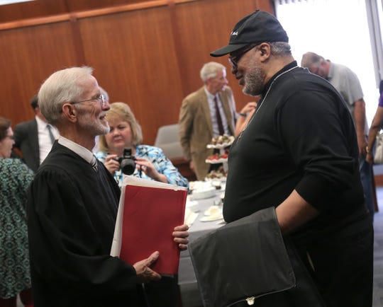 Judge James DeWeese talks with Robert Buggs, a former bailiff of his, during a reception for his 28 years of service at Richland County Common Pleas on Thursday.
