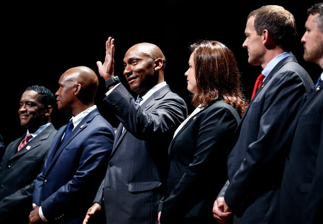 Lee Harris (middle) waves to the crowd before being sworn in as the new mayor of Shelby County during a ceremony Thursday afternoon at the Cannon Center of the Performing Arts in Memphis.